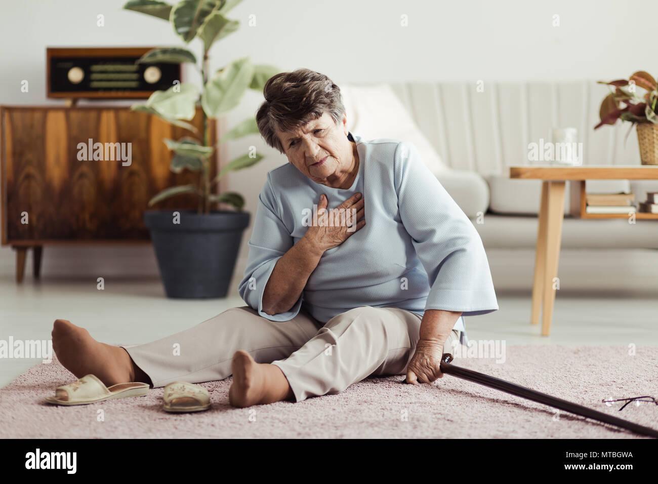Disabilitato il sambuco signora seduta sul pavimento con un bastone da passeggio e tenendo premuto il suo torace dopo la caduta verso il basso Foto Stock