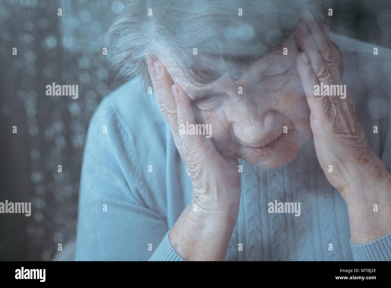 Senior donna con mal di testa, tenendo la testa con le mani Immagini Stock