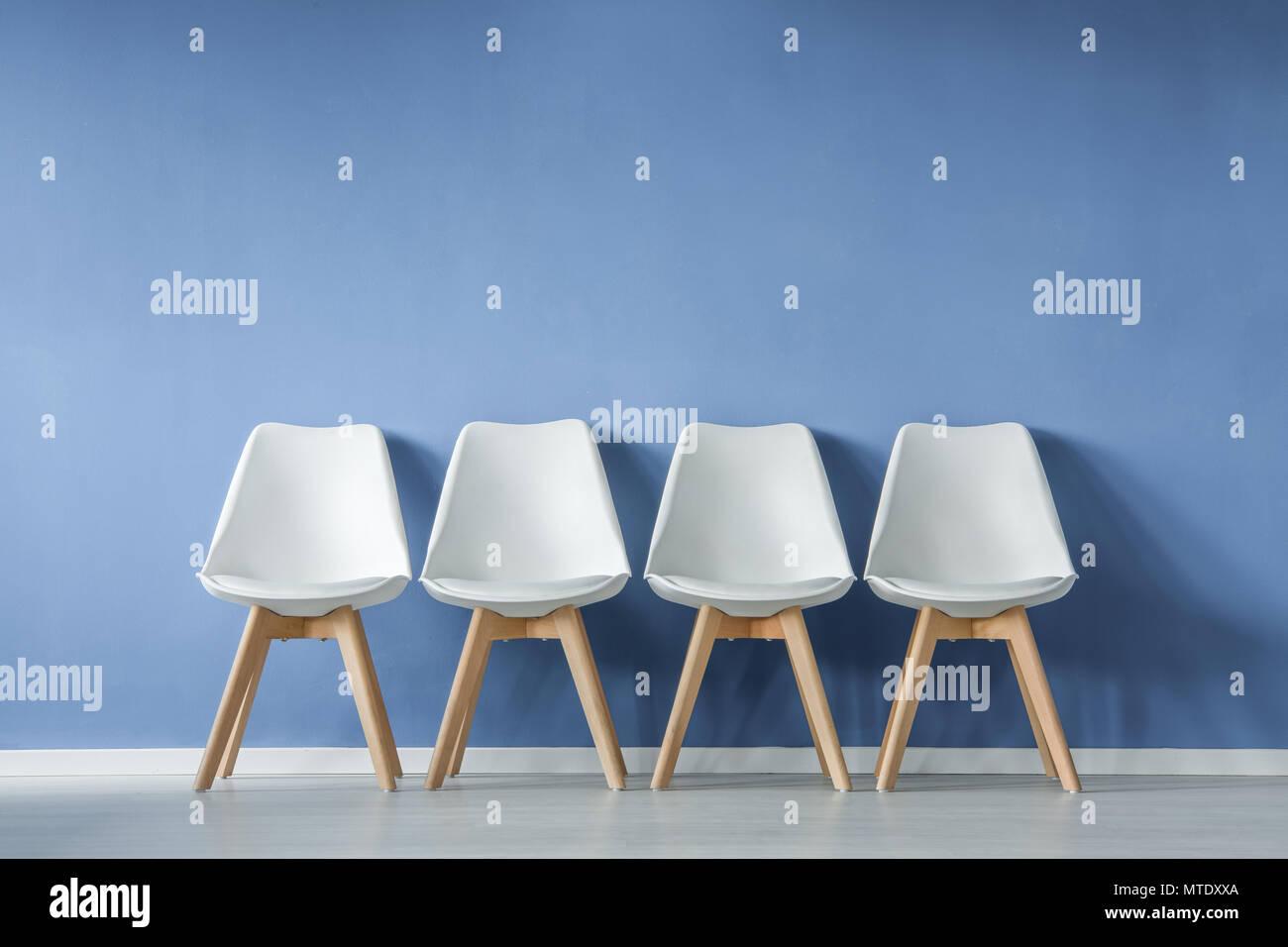 Vista frontale di una fila di moderni semplici sedie bianche