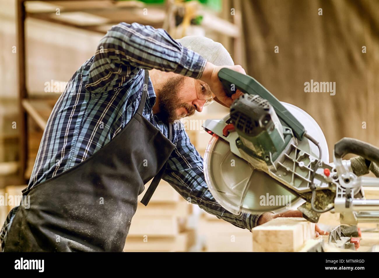 Carpenter lavorare con sega circolare per il taglio di pannelli, l'uomo sawed bar, costruzione e ristrutturazione di casa, riparazione e costruzione utensile Immagini Stock