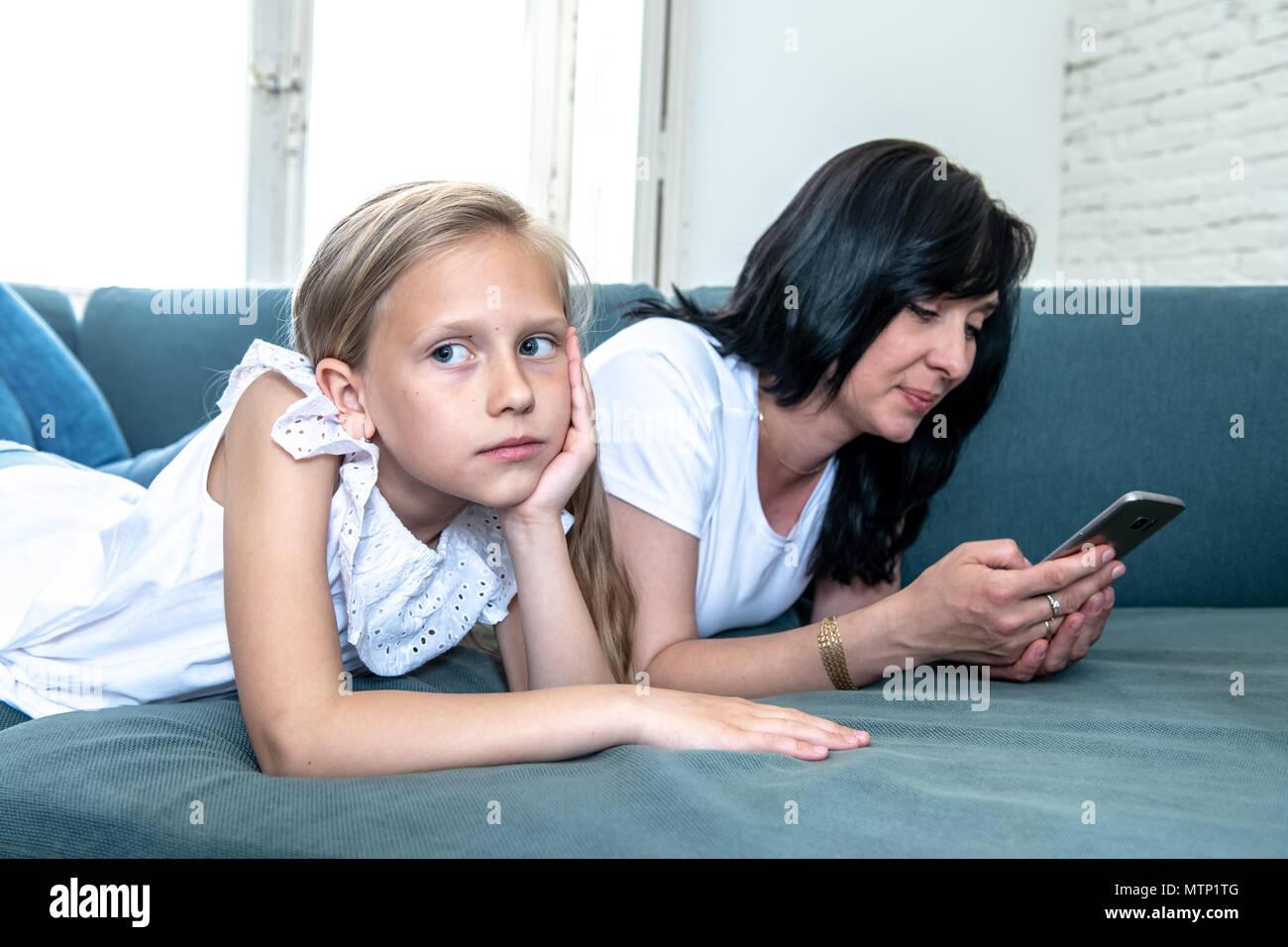 La tecnologia digitale di tossicodipendenti la mamma con il suo smart phone ignorando il suo triste bambina sentendosi abbandonato e infelice con la mamma non prestando attenzione a Immagini Stock
