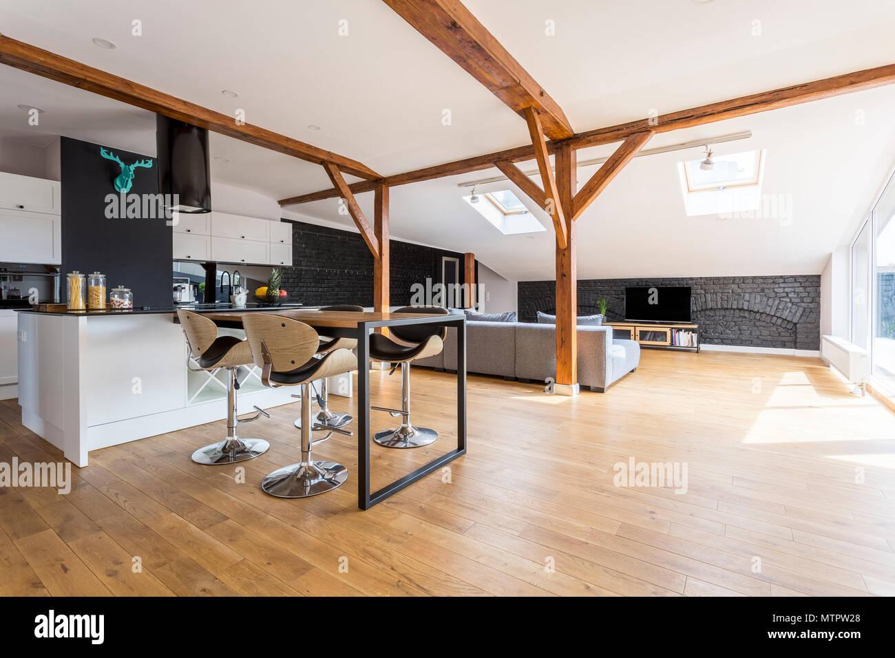 Stanza stretta e lunga con mobili della cucina lineare e tavolo