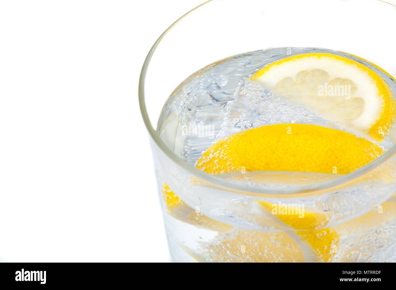 Un bicchiere di vetro con acqua cristallina, limone e cubetti di ghiaccio. Immagini Stock