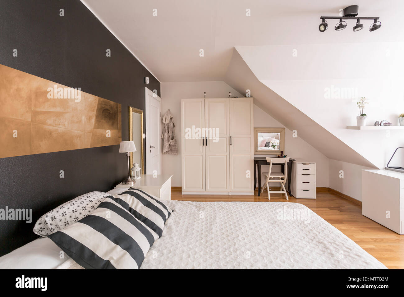 Spaziosa camera da letto mansarda con nero e pareti bianche, letto ...