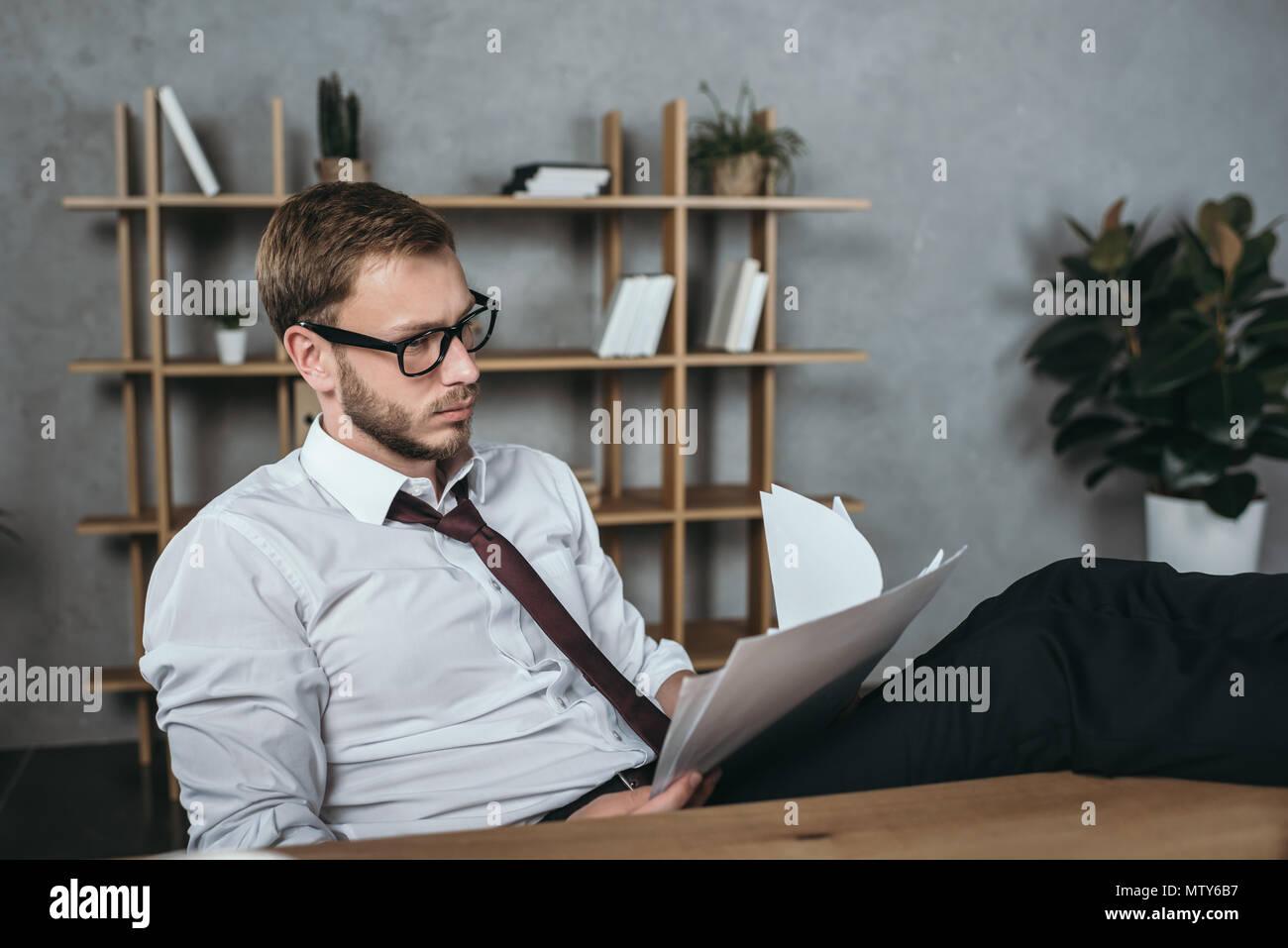 Giovane imprenditore in abbigliamento formale documentazione facendo mentre è seduto in un ufficio moderno Immagini Stock
