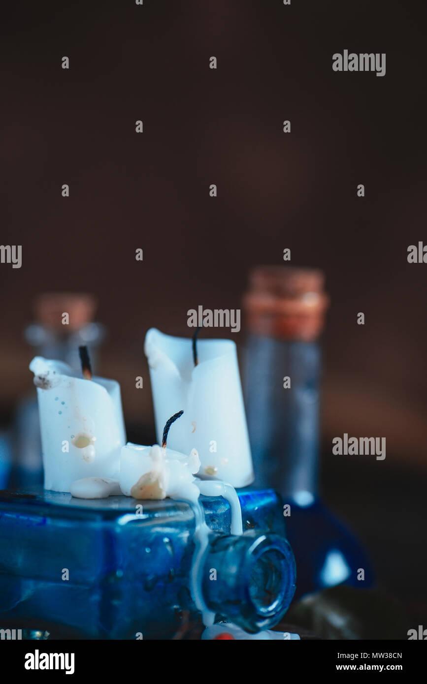 Estinta white candele di cera in un magico ancora in vita con pozioni e Moss. Concetto occulto con copia spazio. Immagini Stock