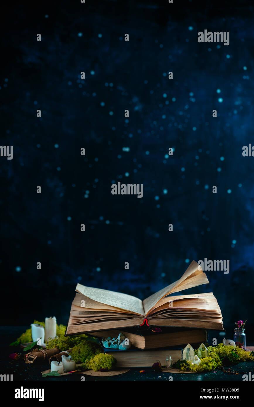 Libro aperto con candele, cristalli e Moss. Lettura del concetto di fantasia con copia spazio. Magica ancora in vita su uno sfondo scuro con apparecchiature occulto. Immagini Stock