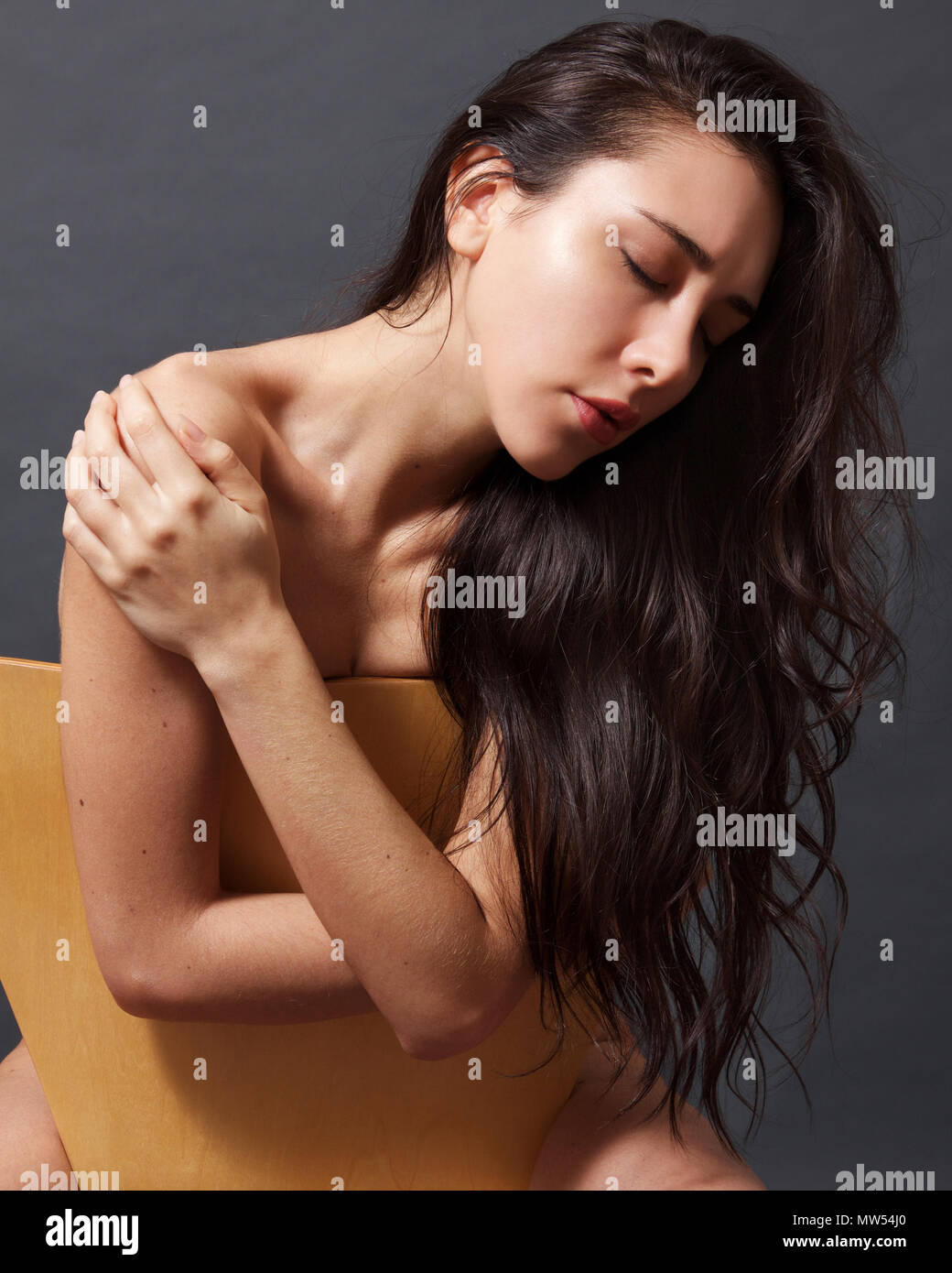 Giovane donna italiana con capelli castani e pieno labbra rosse e abbattuto gli occhi seduti su una sedia Immagini Stock