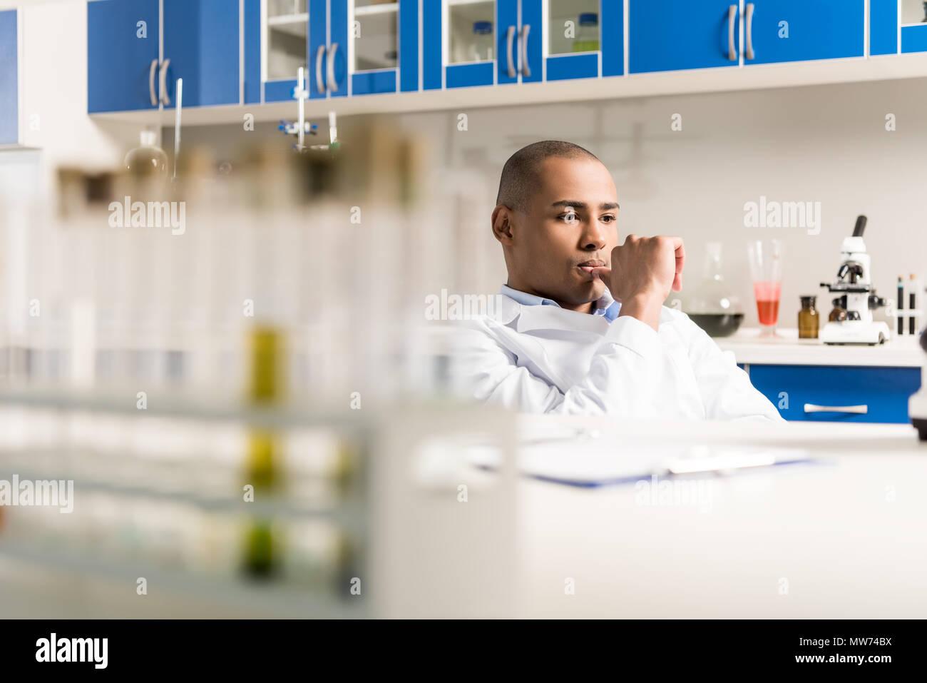 Scienziato maschio durante il lavoro al moderno laboratorio biologico seduta con la mano sul mento Immagini Stock