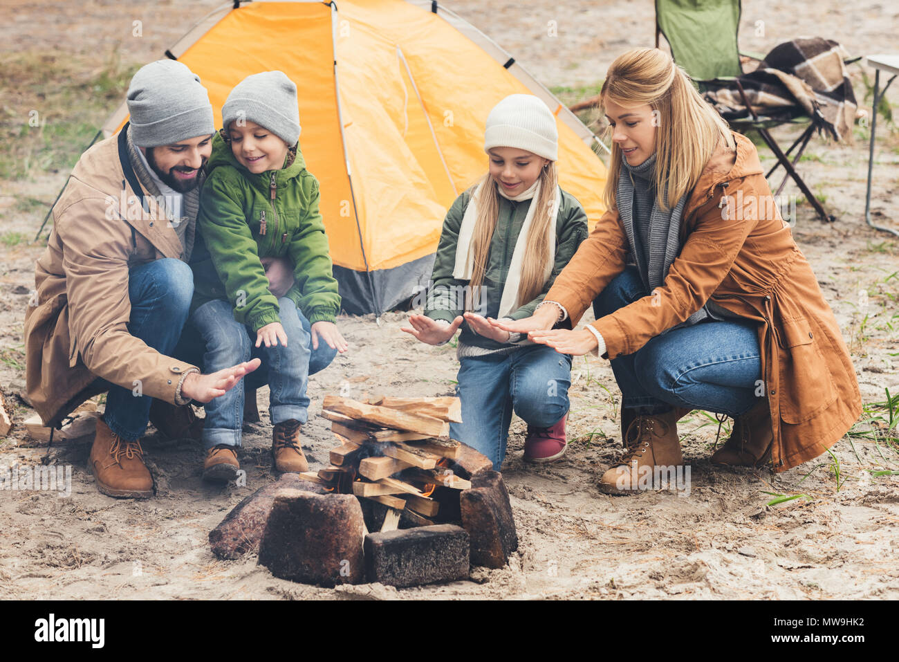 Il riscaldamento della famiglia con il fuoco pur avendo viaggio sulla giornata autunnale Immagini Stock
