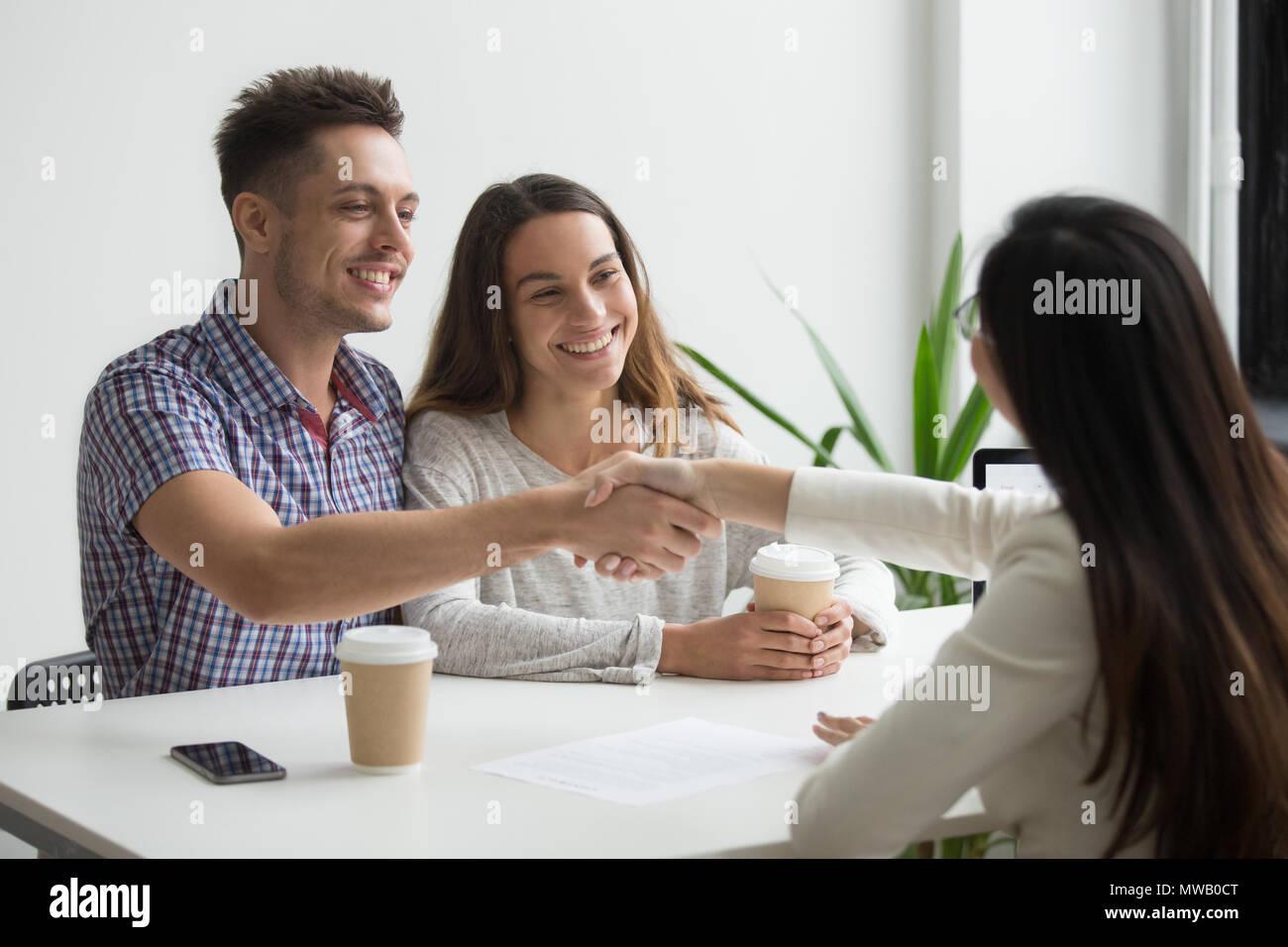 Sorridente coppia millenario realtor di handshaking o advisor facendo Immagini Stock