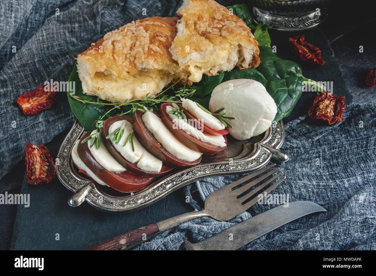 Focaccia italiana con formaggio, rosmarino, mozzarella e pomodoro. Messa a fuoco selettiva. Close-up. Il telaio orizzontale. Immagini Stock