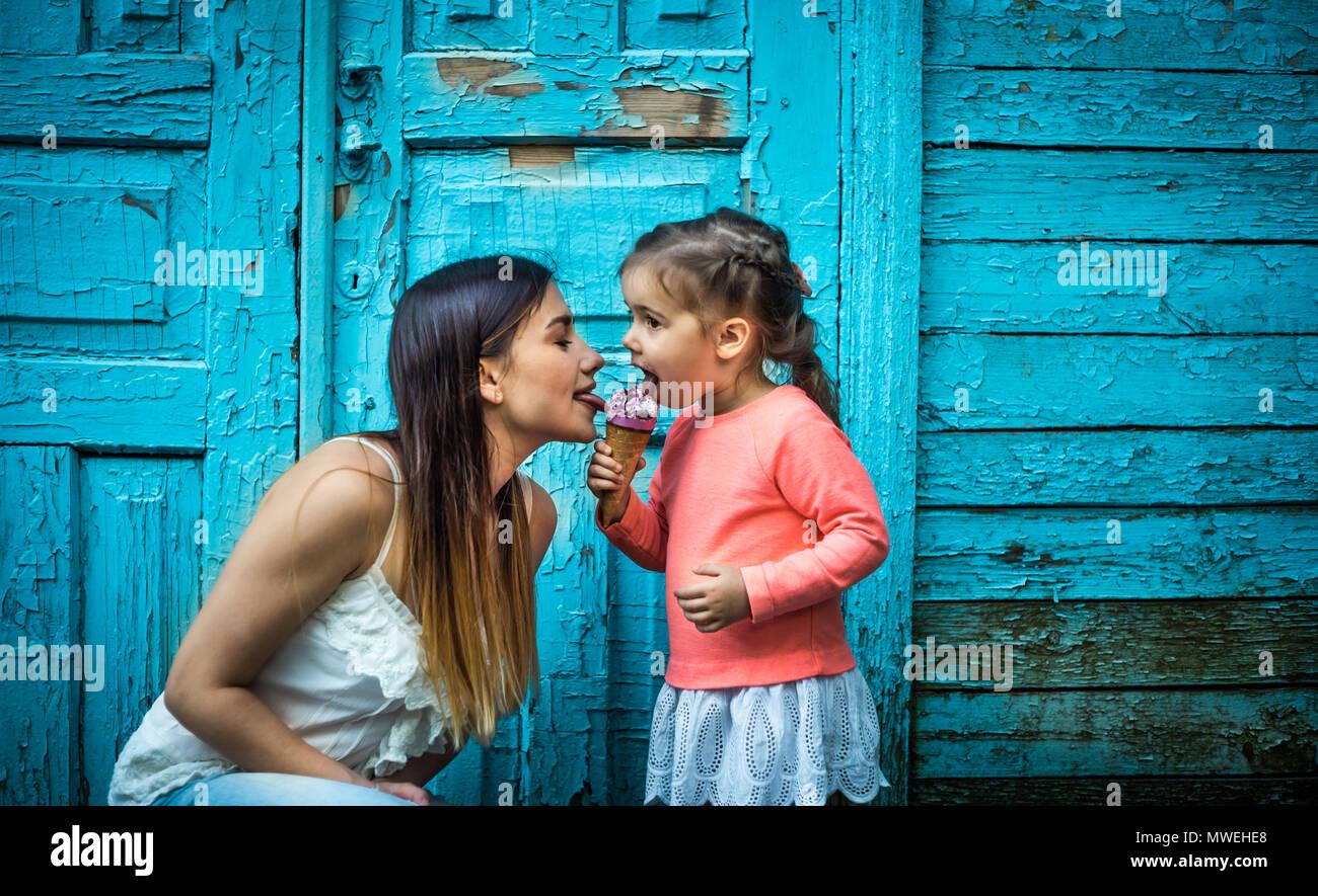 Bambina con la madre a mangiare il gelato su un bellissimo sfondo turchese del legno Immagini Stock