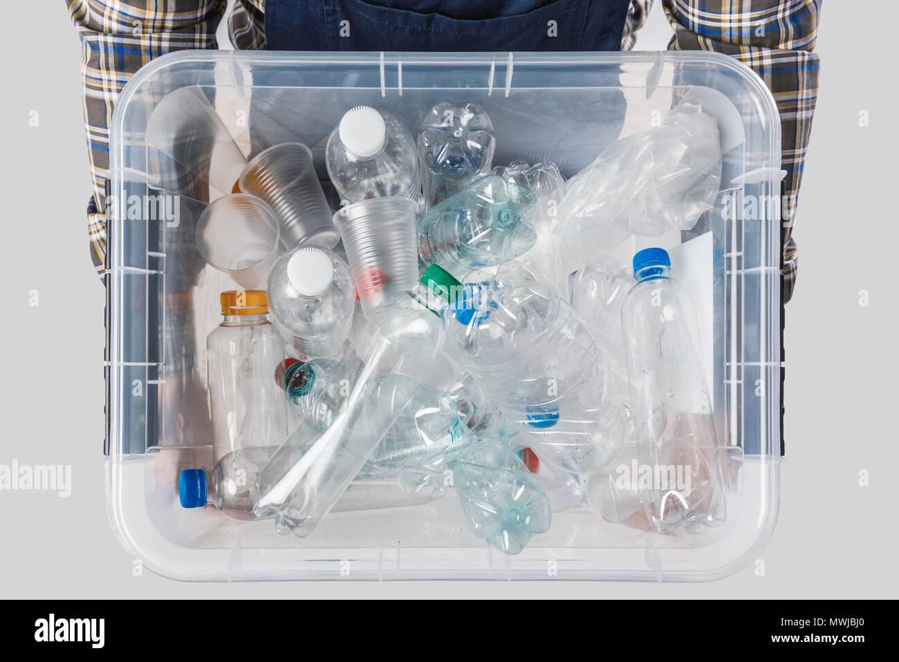 Vista parziale dell'uomo tenendo il contenitore con le bottiglie di plastica in mani isolate su grigio, concetto di riciclaggio Immagini Stock