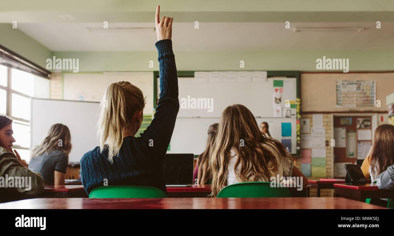 Vista posteriore della studentessa seduti in classe e alzando la mano fino a porre domande durante la lezione. Studente di scuola superiore si solleva la mano e chiede docente Immagini Stock