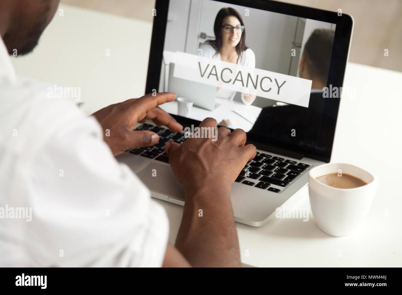 Close up uomo nero risponde a aprire la posizione di lavoro online Immagini Stock