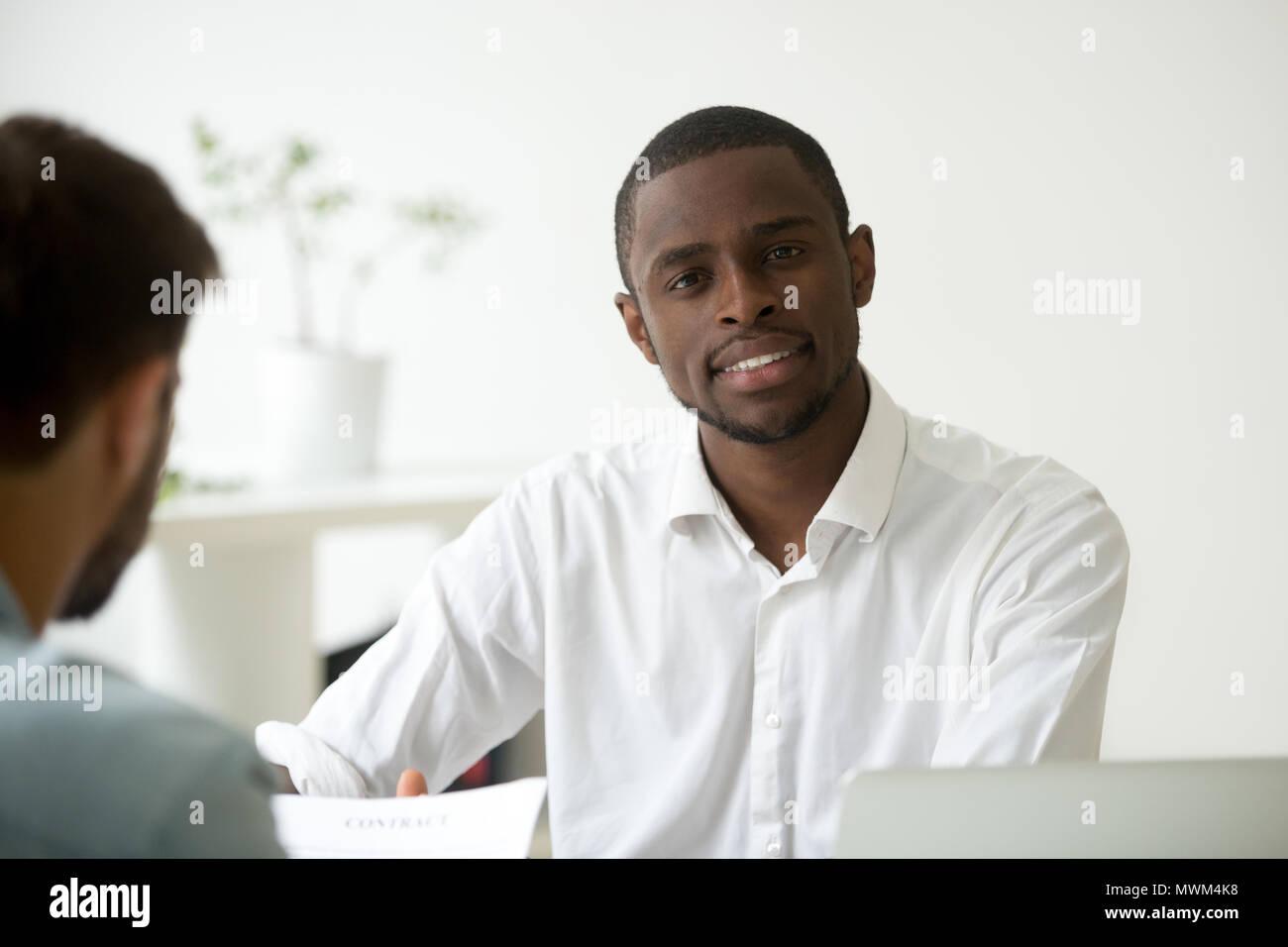 Sorridente African American lavoratore guardando la fotocamera in ufficio Foto Stock