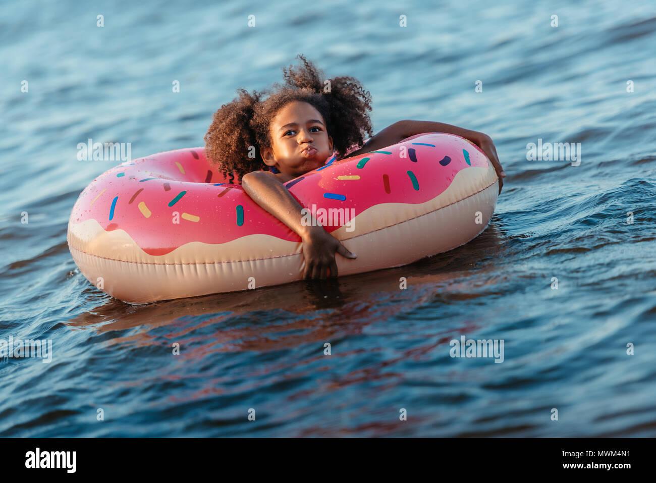 Carino African American Girl nuotare in un anello in gomma e sorridente in telecamera Immagini Stock