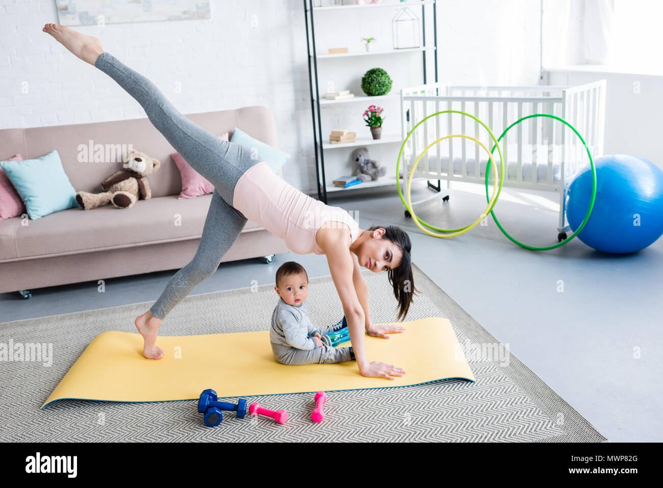 53e344e0a157 Giovane madre la pratica dello yoga in uno zampe cane Downward-Facing  pongono mentre il suo piccolo bambino seduto sul tappeto a casa