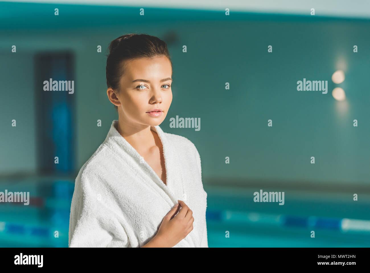 Bella giovane donna in accappatoio davanti alla piscina spa Immagini Stock