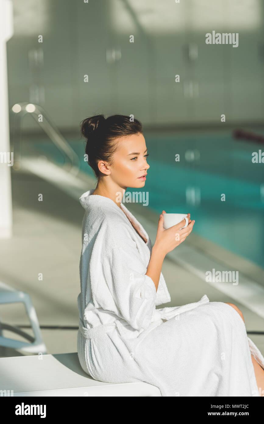 Bella giovane donna in accappatoio con tazza di caffè a spa Immagini Stock