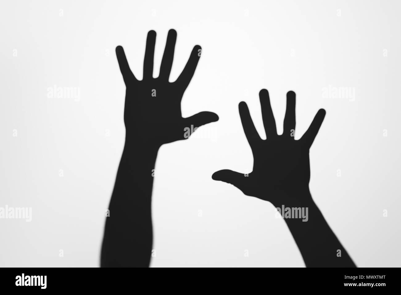 Ombre misteriose di mani umane su grigio Immagini Stock