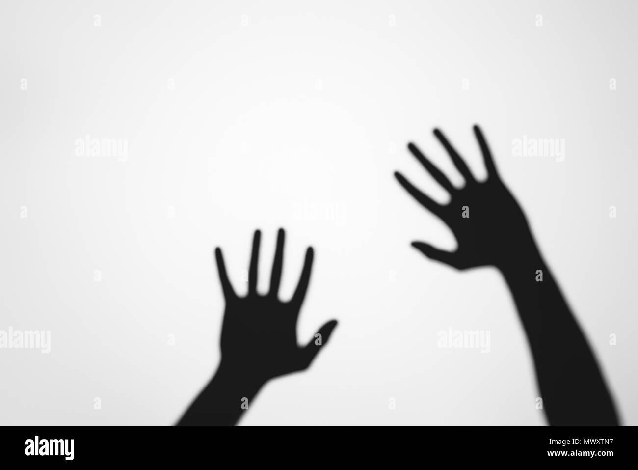 Spooky misteriose ombre di mani umane su grigio Immagini Stock