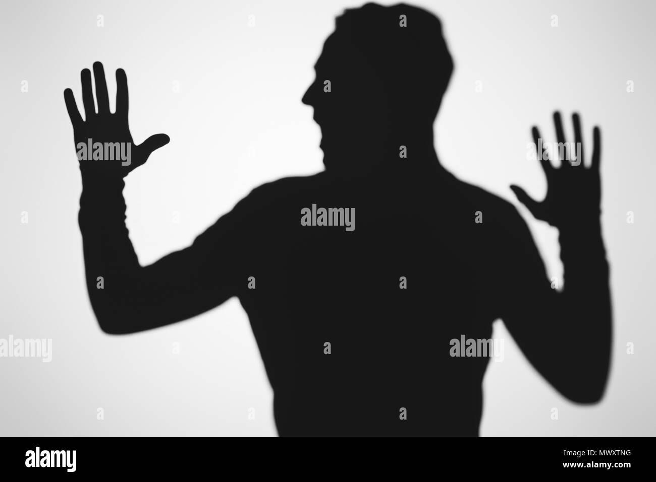 Scary sfocata ombra della persona urlando su grigio Immagini Stock