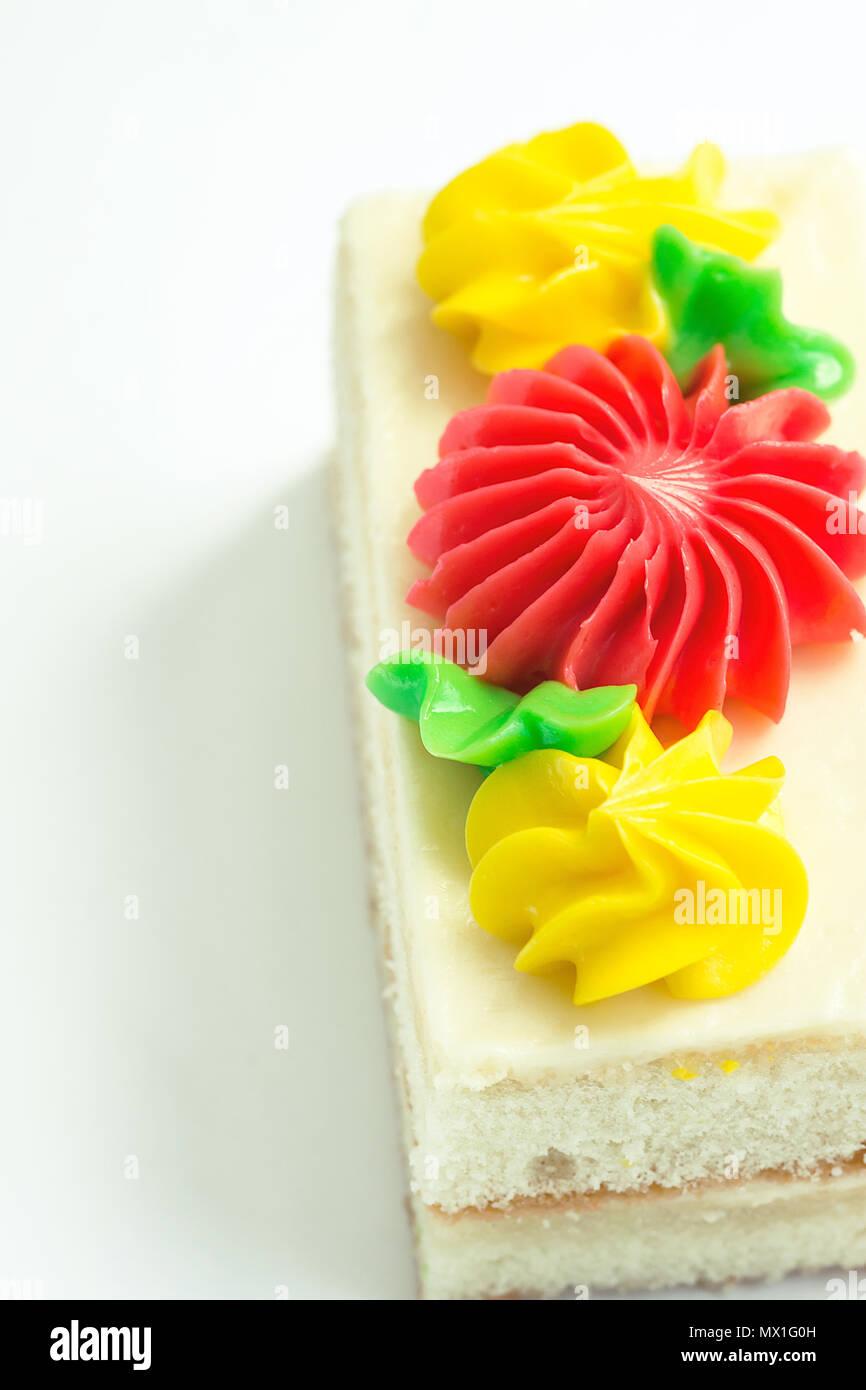 Sezione rettangolare di strato di spugna la torta con panna montata Crema  di burro la glassa. Decorate con Rosso Giallo Daisy fiori e foglie verdi.