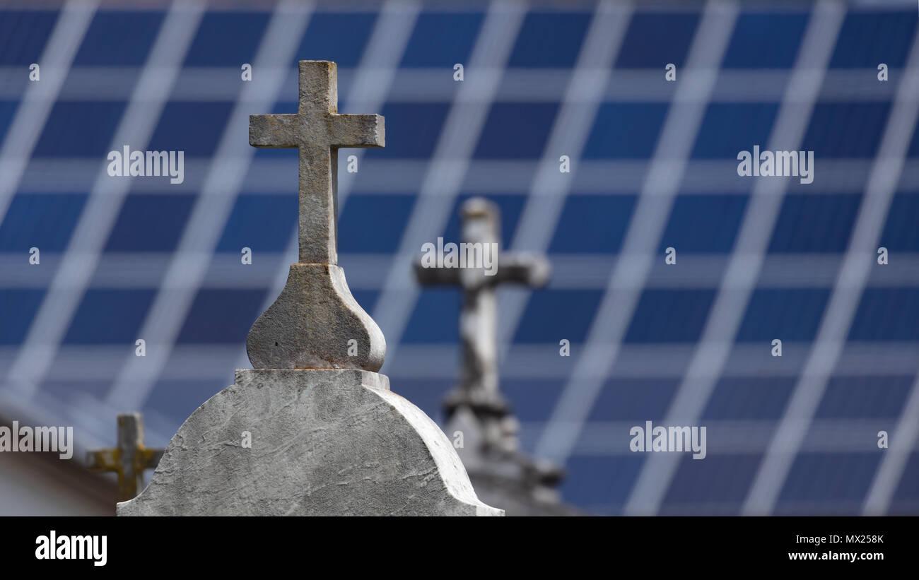 Croci in pietra sulle tombe con sfocate pannelli solari in background Immagini Stock