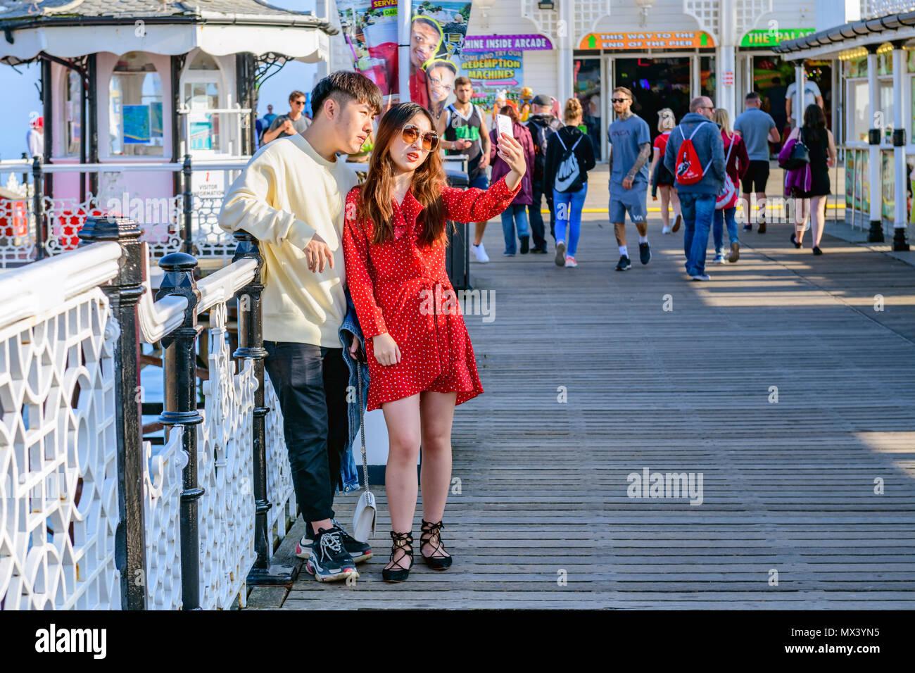 Un asiatico oriental matura in posa per una selfie sul molo di Brighton Immagini Stock