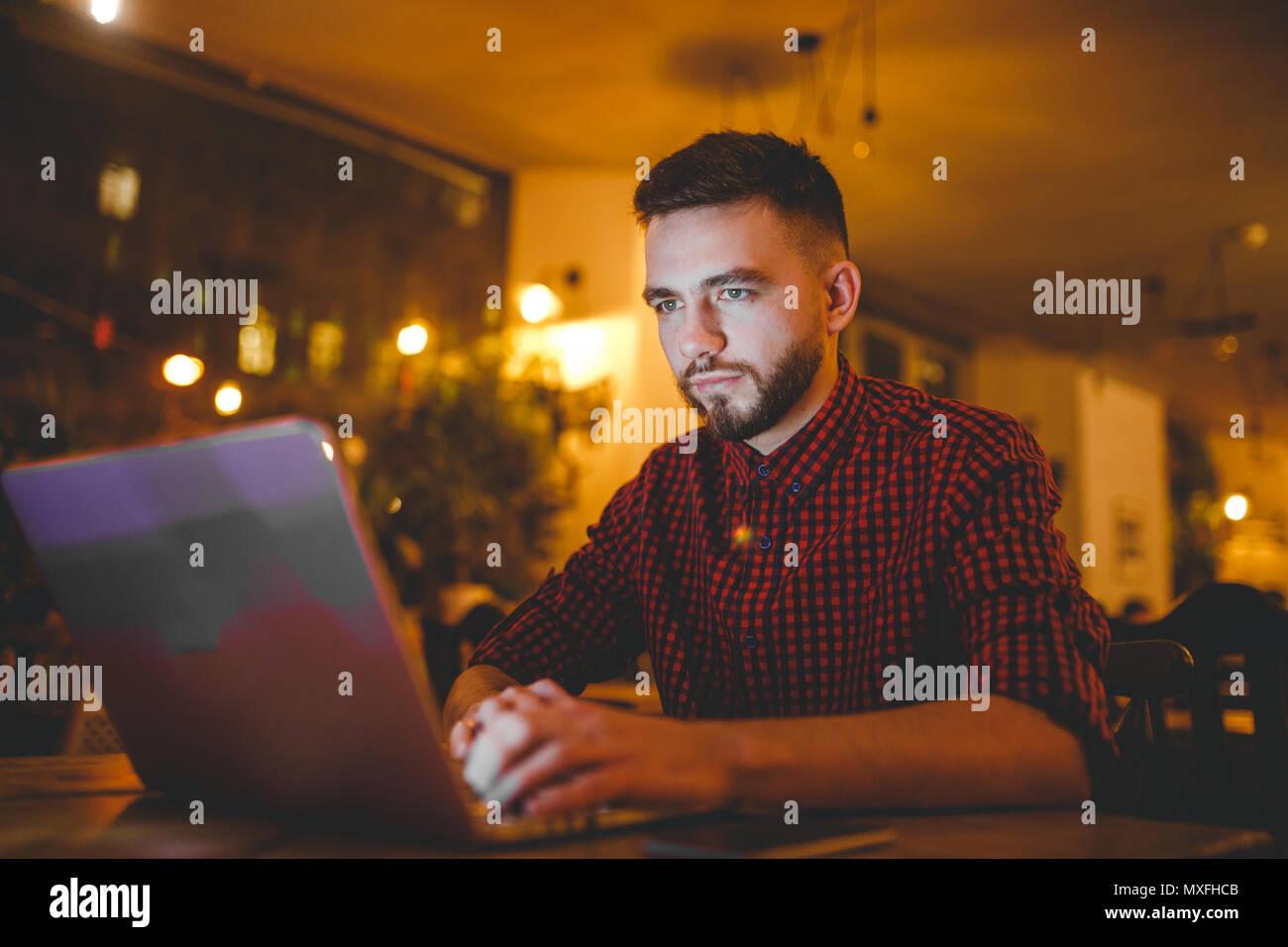 Un bel giovane uomo caucasico con la barba e sorriso toothy in rosso una camicia a scacchi sta lavorando dietro un grigio laptop seduti ad un tavolo di legno. Le mani sulla tastiera. In serata presso la caffetteria Immagini Stock