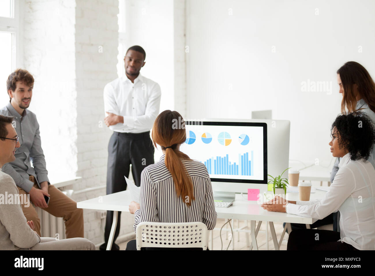 Femmina leader del team a parlare con i colleghi circa il nuovo progetto Immagini Stock