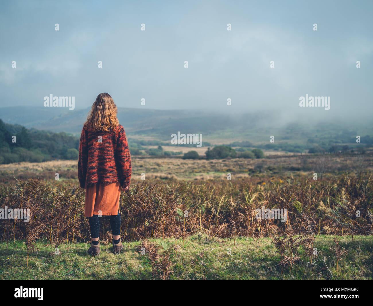 Una giovane donna è in piedi su un moro in autunno Immagini Stock