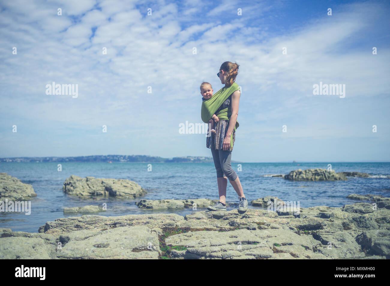 Una giovane madre sta camminando lungo la costa con il suo bambino in una imbracatura Immagini Stock