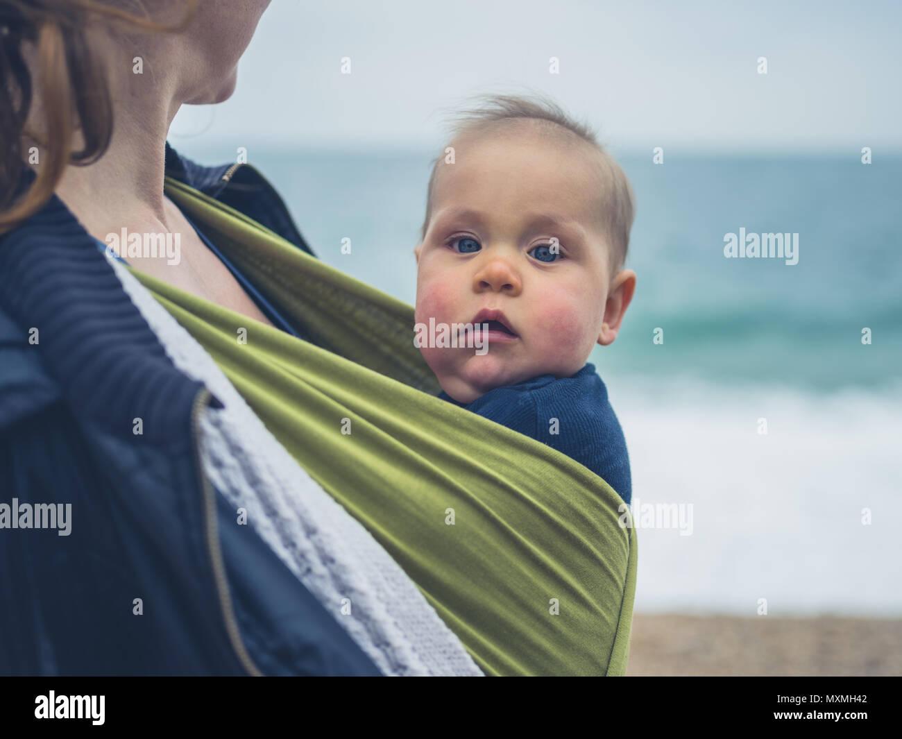 Una madre è sulla spiaggia con il suo bambino in una imbracatura Immagini Stock