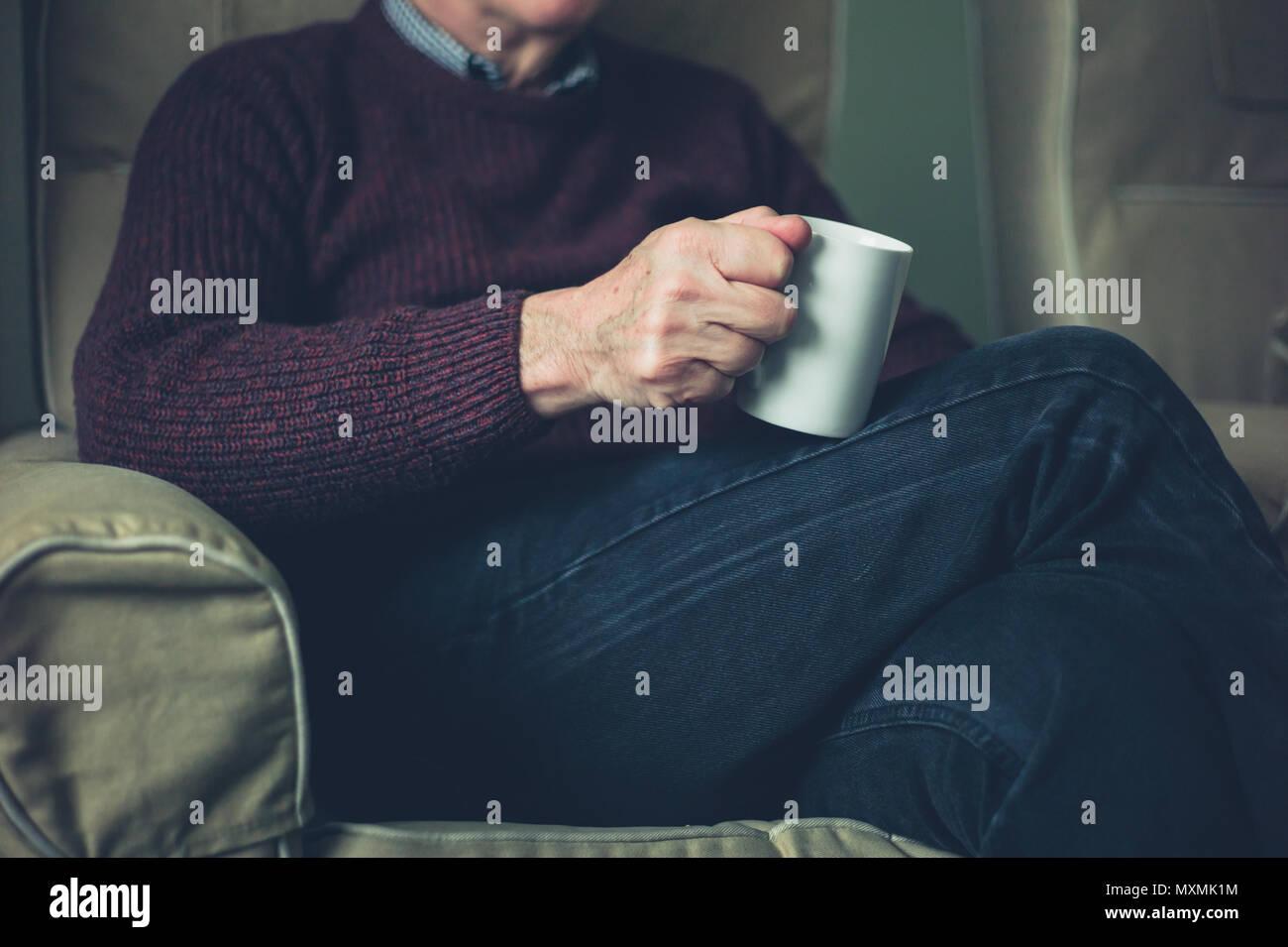 Un anziano uomo è in un momento di relax a casa con una tazza di tè Immagini Stock