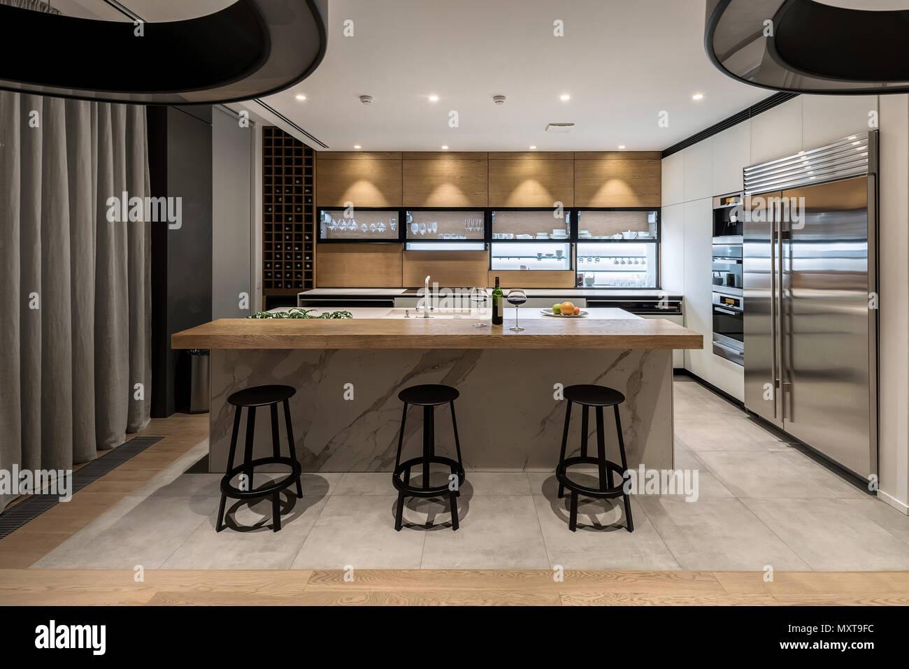 Cucina in stile moderno con pareti chiare e un parquet in legno e