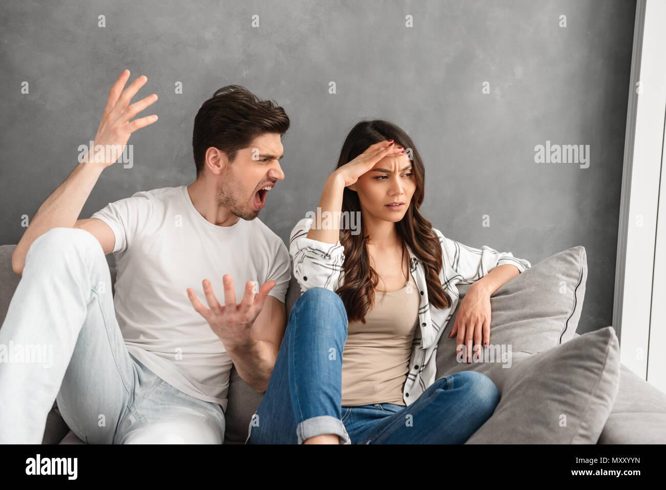 Foto di deluso giovane seduti insieme sul divano di casa mentre l'uomo grida sulla donna con colpa isolate su sfondo bianco Immagini Stock