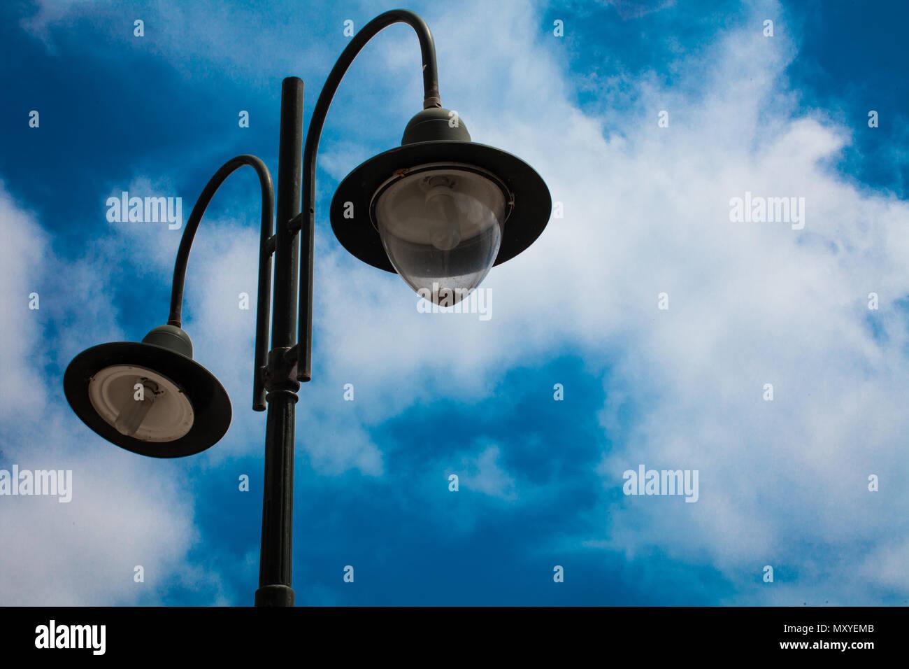 La luce post con due lampadine e blu cielo nuvoloso sfondo