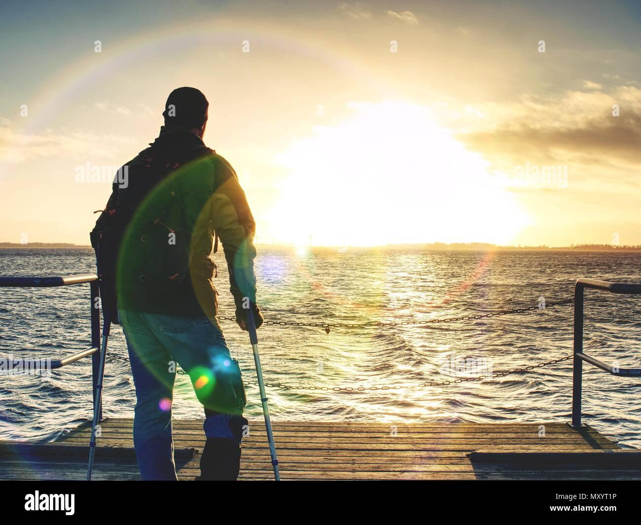 Escursionista con la medicina stampella e gamba fissata in un immobilizzatore a piedi su wharf Pier. L'uomo ha fissato gamba rotta in gesso. Felice l'uomo disabili sulla spiaggia a piedi. Len Immagini Stock