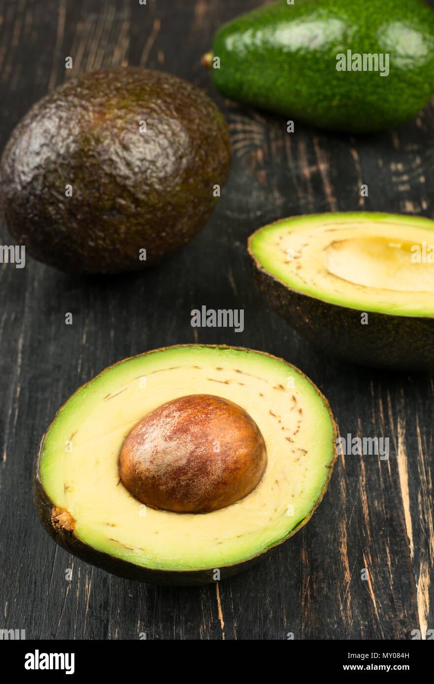 Disperdere la metà di avocado e frutti su sfondo di legno Immagini Stock