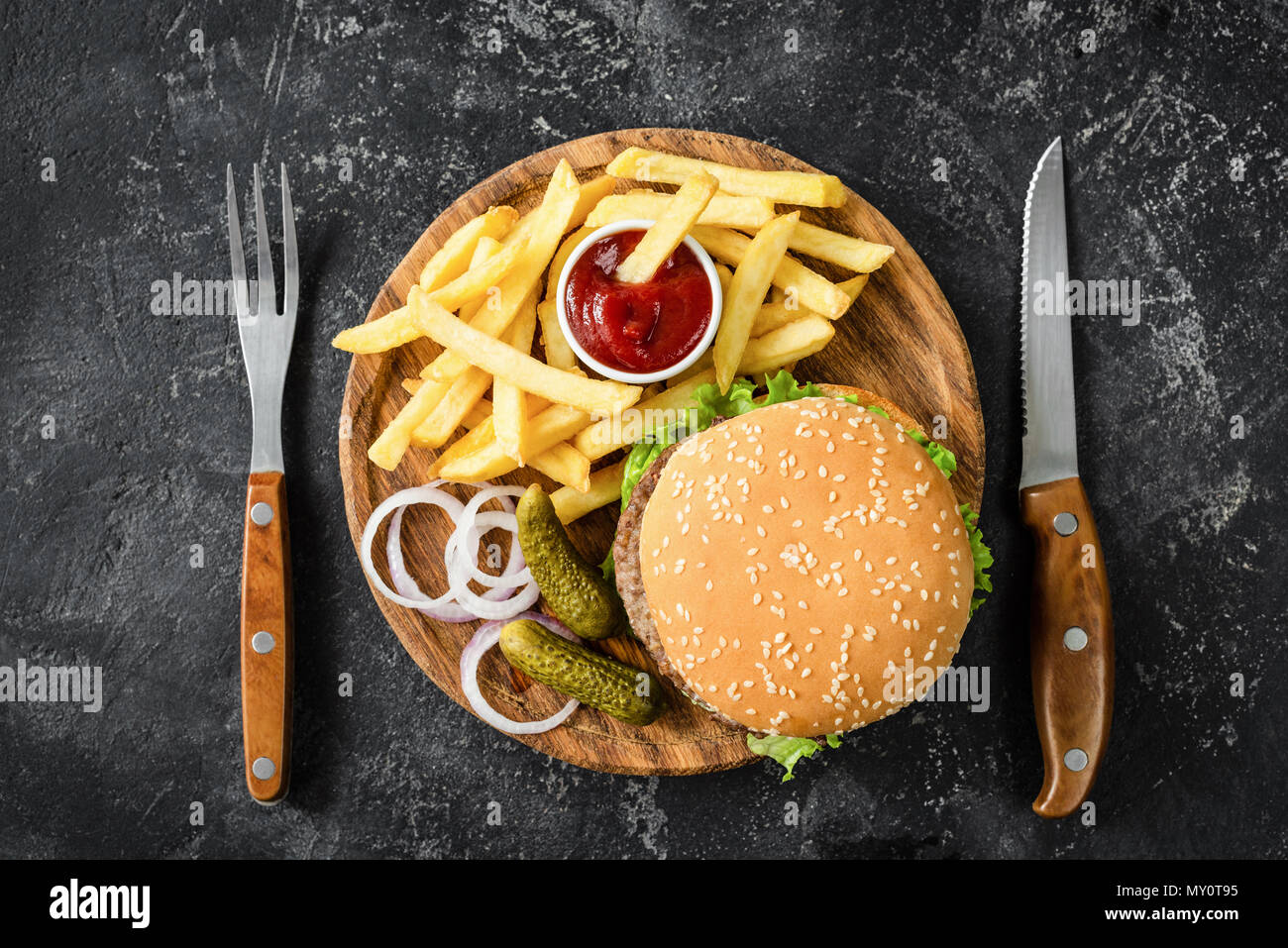 Hamburger di manzo, patate fritte, sottaceti, cipolla e ketchup. Tabella vista dall'alto. Concetto di fast food Immagini Stock