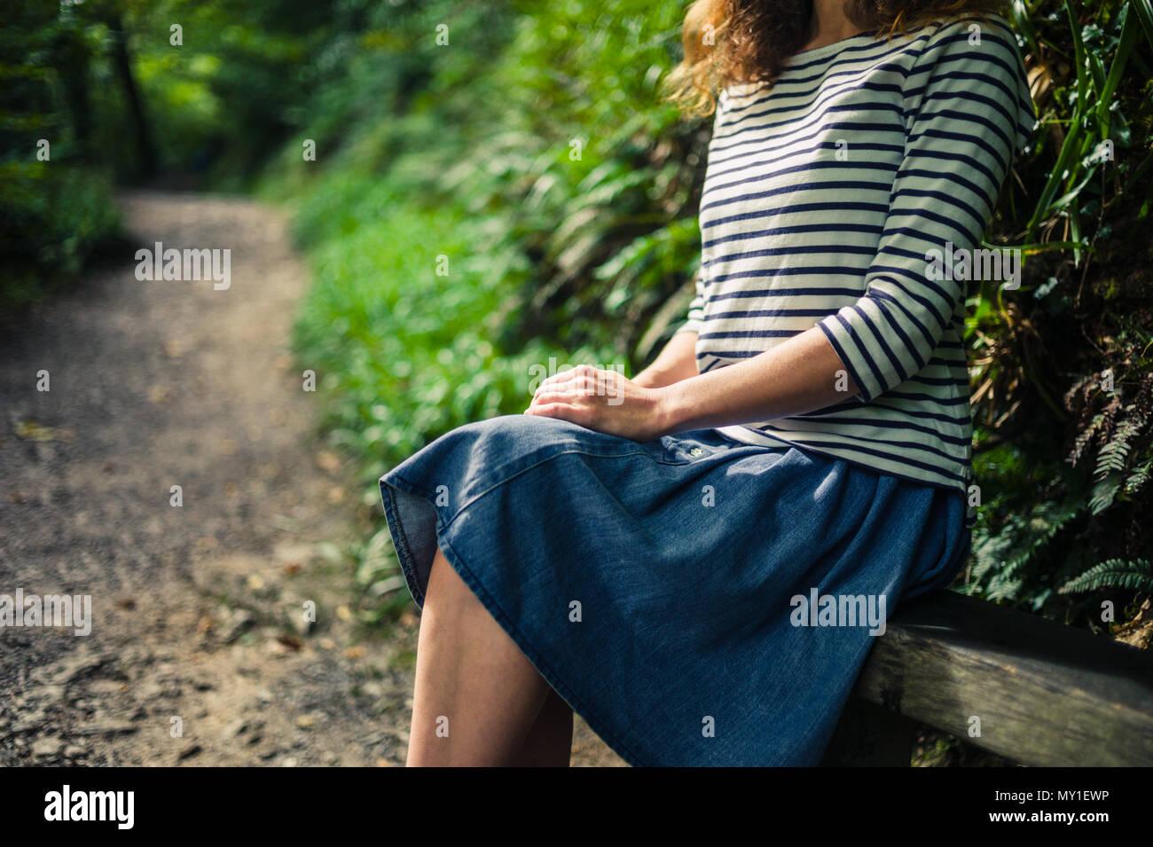 Una giovane donna è seduta e appoggiata su un banco nella foresta Immagini Stock