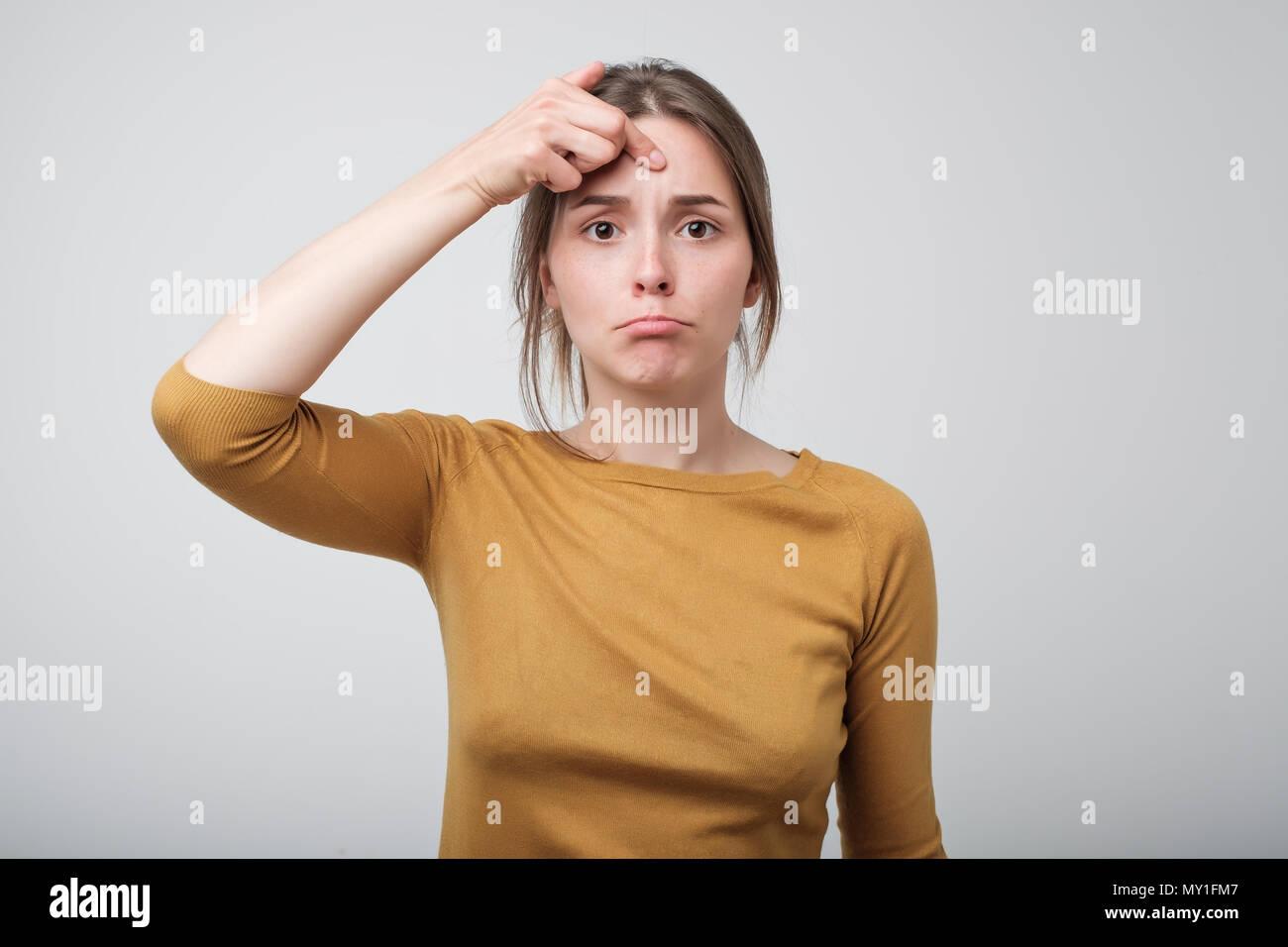 Deluso giovane donna che guarda la fotocamera. Immagini Stock
