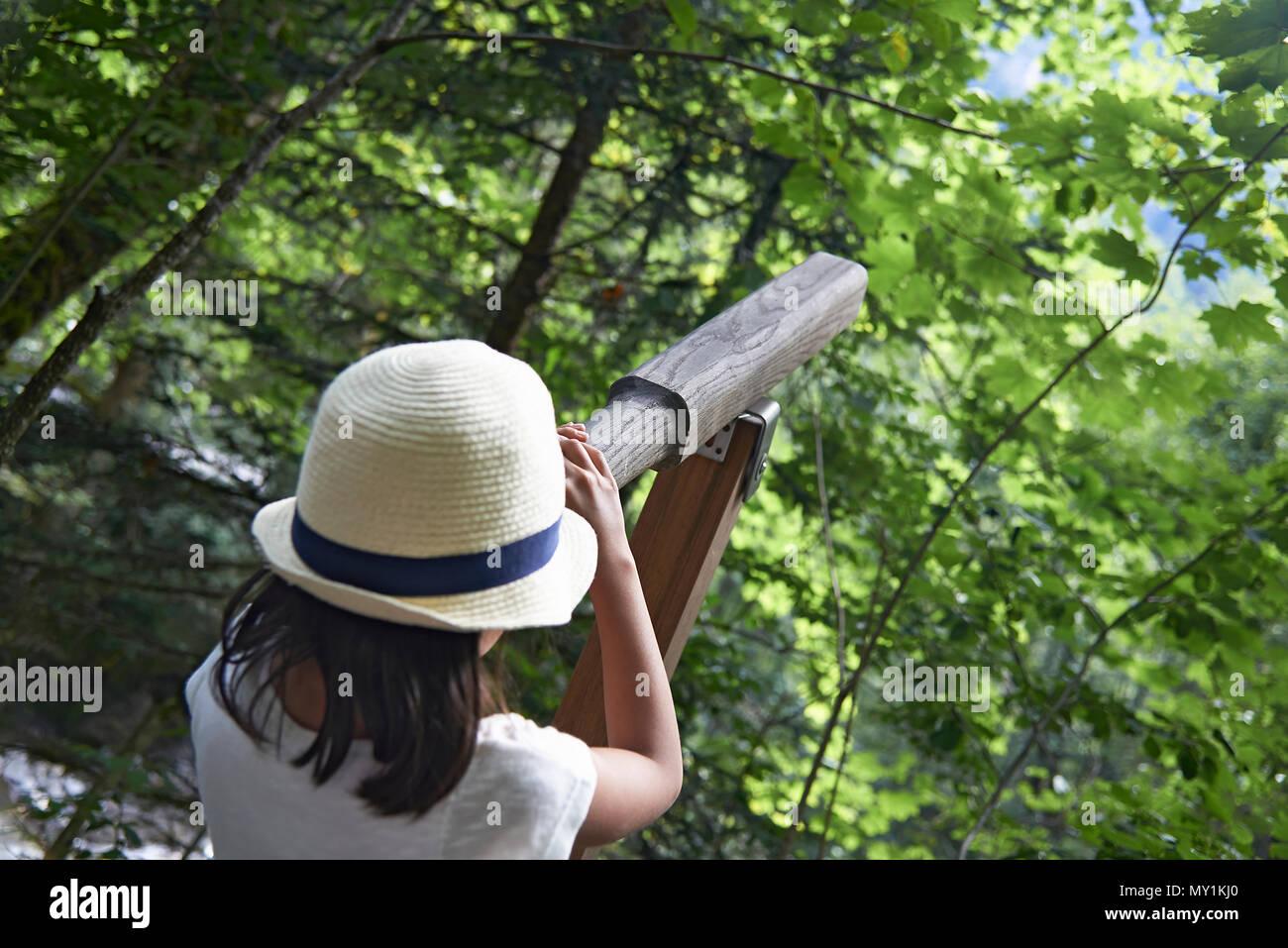 Oltre la spalla colpo di una giovane ragazza cerca attraverso un binocolo nella foresta alla ricerca di uccelli e altri la vita in natura Foto Stock