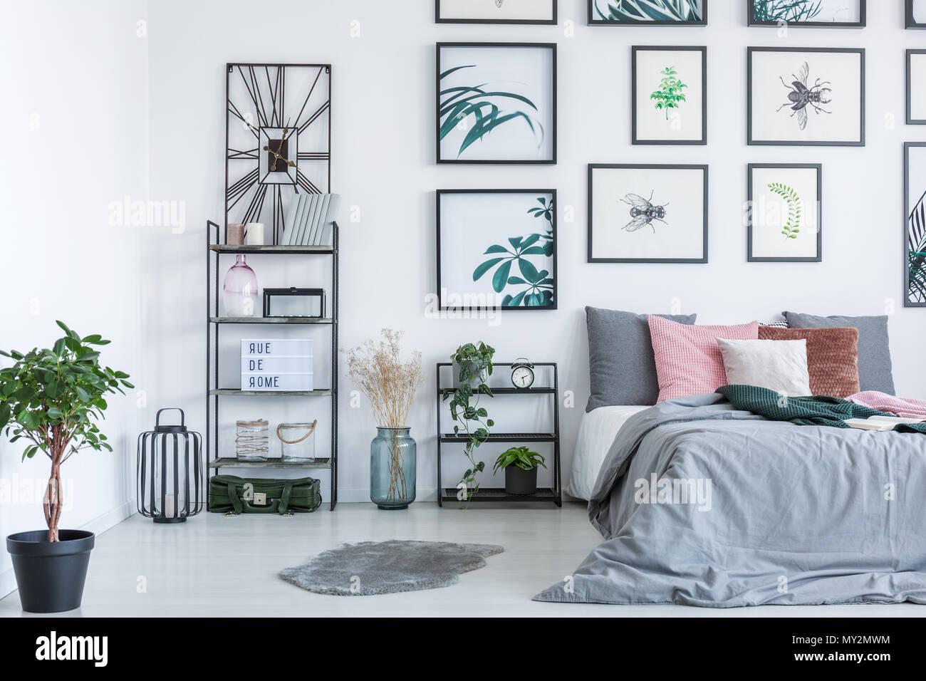 Foto reale di un letto in piedi accanto a ripiani con ornamenti e