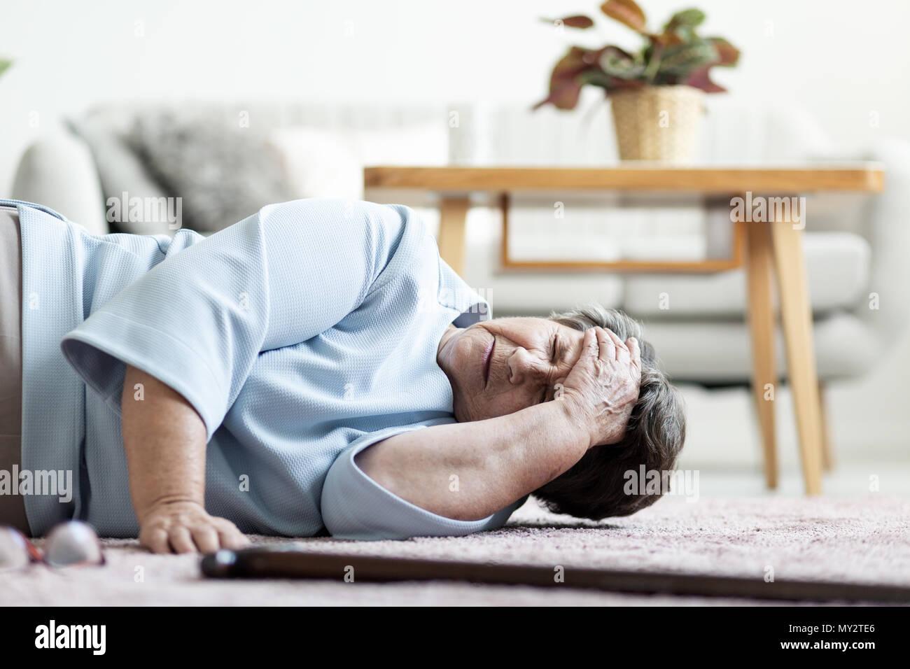 Senior donna con un mal di testa dopo la caduta verso il basso a casa Foto Stock