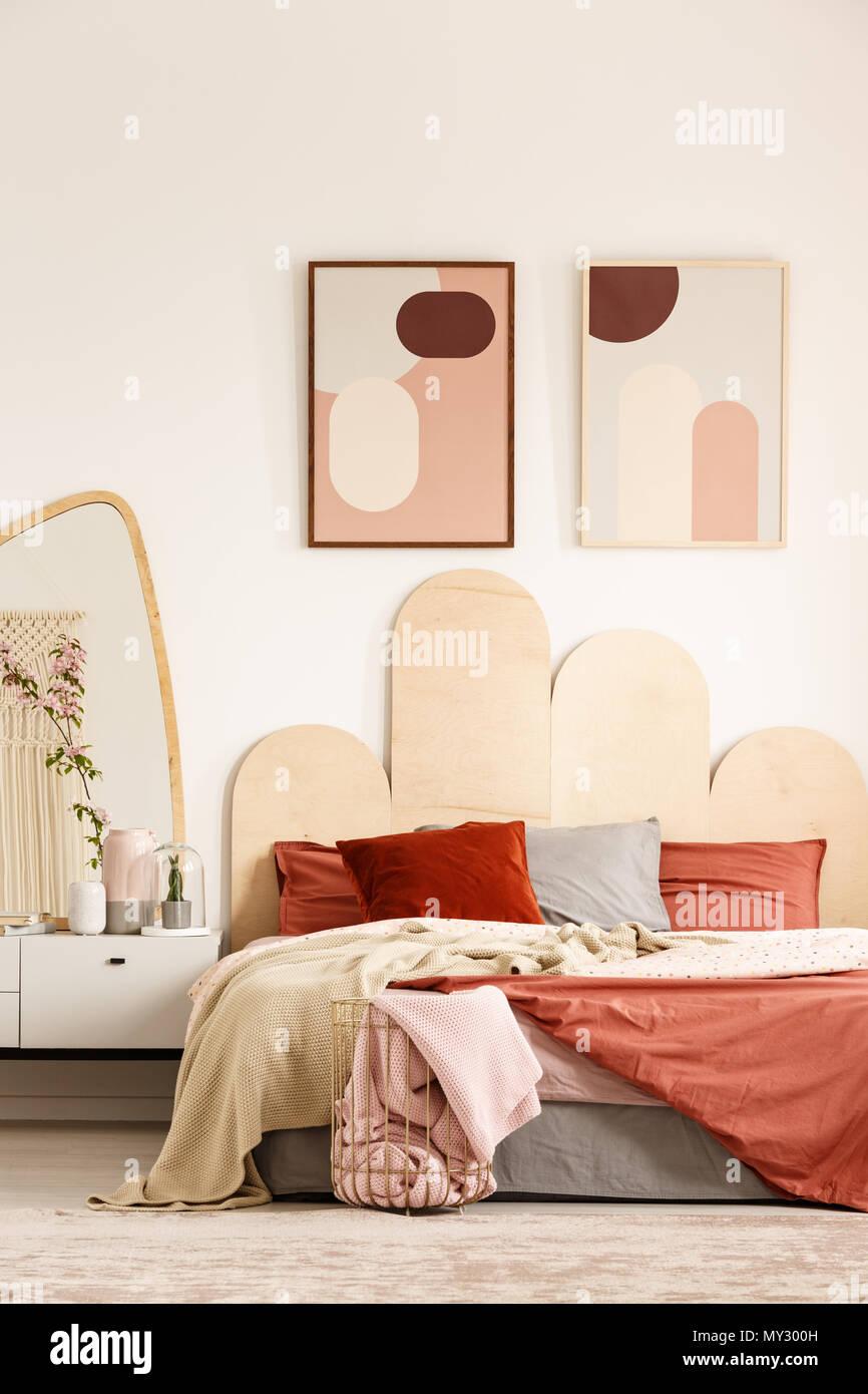 Poster sopra il letto arancione accanto al bianco armadio con ...