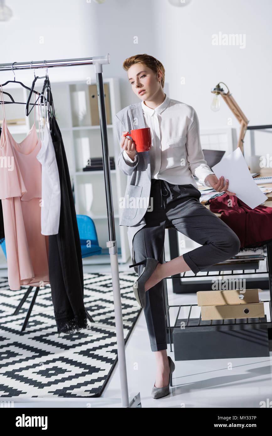 b135fa5a0805 Elegante giovani designer di moda seduto sulla scrivania in ufficio e  guardando abiti
